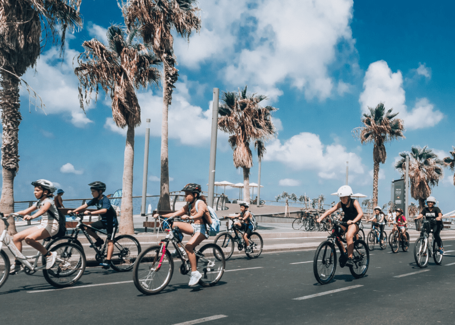 several kids riding bikes against a backdrop of palm trees on a road